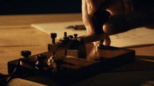 dolly closeup of a telegrapher using a morse code key (0;00;06;09)